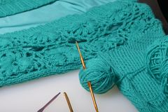 Strings of thread for knitting emerald color and hooks for knitting. Lie on a ready knitted product. Strings of thread for knitting emerald color and hooks for stock images
