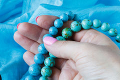 Strings of turquoise beads on blue silk Stock Image