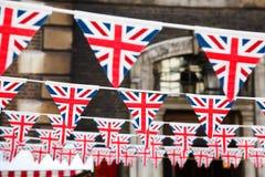 Strings of Union Jack bunts festive decoration in London England. Union Jack flag triangular bunting hanging in a street, a festive decorations in London England stock image