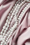 Pearl on silk. Strings of white pearl on crumpled pink silk closeup stock image