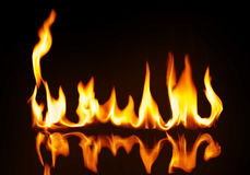 A strip of fire on the reflecting surface. On a black background Stock Image