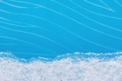 A strip of natural snow on blue glass winter background Stock Image