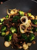 Strip Steak Veggie Stir Fry. Marinated strip steak with broccoli, water chest nuts, onions, and garlic in stir fry pan. Steak and veggies have caramelized and Stock Photo