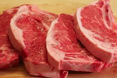 Strip steaks. Four strip steaks on a cutting board, ready for the grill Stock Photography