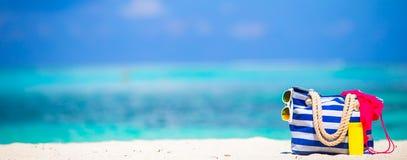 Stripe сумка, голубое полотенце, солнечные очки, солнцезащитный крем Стоковая Фотография