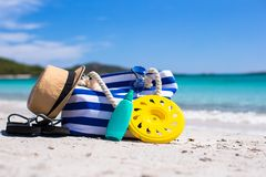 Stripe bag, straw hat, sunblock and frisbee on. Beach bag, straw hat, sunscreen and a frisbee on the white sandy tropical beach Royalty Free Stock Photography
