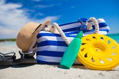 Stripe bag, straw hat, sunblock and frisbee on. Beach bag, straw hat, sunscreen and a frisbee on the white sandy tropical beach Royalty Free Stock Image