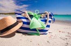 Stripe bag, straw hat, sunblock and frisbee on. Beach bag, straw hat, sunscreen and a frisbee on the white sandy tropical beach Royalty Free Stock Photo