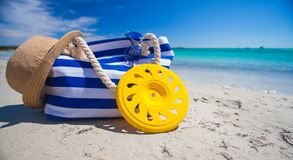 Stripe bag, straw hat, sunblock and frisbee on. Beach bag, straw hat, sunscreen and a frisbee on the white sandy tropical beach Royalty Free Stock Images