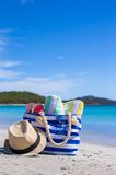 Stripe bag, straw hat, sunblock and frisbee on. Beach bag, straw hat, sunscreen and a frisbee on the white sandy tropical beach Stock Photography