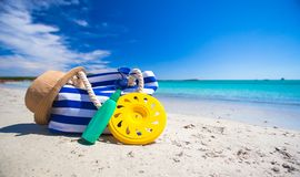 Stripe bag, straw hat, sunblock and frisbee on. Beach bag, straw hat, sunscreen and a frisbee on the white sandy tropical beach Stock Image