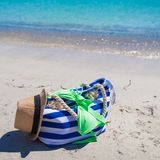 Stripe bag, straw hat, sunblock and frisbee on Royalty Free Stock Photo