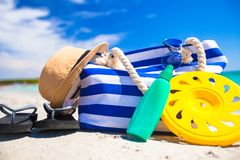 Stripe bag, straw hat, sunblock and towel on beach. Beach bag, straw hat, sunscreen and a frisbee on the white sandy tropical beach Stock Image