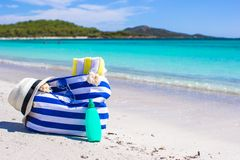 Stripe bag, straw hat, sunblock and towel on beach. Beach bag, straw hat, sunscreen and a frisbee on the white sandy tropical beach Royalty Free Stock Images