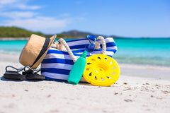 Stripe bag, straw hat, sunblock and towel on beach Stock Image
