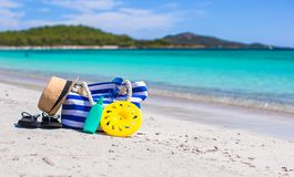 Stripe bag, straw hat, sunblock and towel on beach. Beach bag, straw hat, sunscreen and a frisbee on the white sandy tropical beach Royalty Free Stock Photos