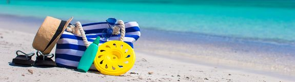 Stripe bag, straw hat, sunblock and towel on beach. Beach bag, straw hat, sunscreen and a frisbee on the white sandy tropical beach Royalty Free Stock Photography