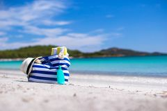 Stripe bag, straw hat, sunblock and towel on white. Beach bag, straw hat, sunscreen and a frisbee on the white sandy tropical beach Stock Image