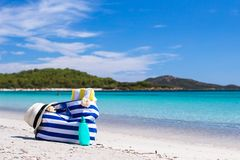 Stripe bag, straw hat, sunblock and towel on white. Beach bag, straw hat, sunscreen and a frisbee on the white sandy tropical beach Stock Photos