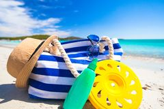 Stripe bag, straw hat, sunblock and towel on white. Beach bag, straw hat, sunscreen and a frisbee on the white sandy tropical beach Stock Photography