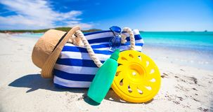 Stripe bag, straw hat, sunblock and towel on white. Beach bag, straw hat, sunscreen and a frisbee on the white sandy tropical beach Stock Photo