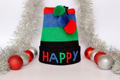 Stripe knit hat with the multi-colored word HAPPY and three pompoms, red and silver Christmas balls and silver tinsel on a neutral. Background. Concept of royalty free stock photo