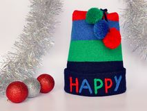 Stripe knit hat with the multi-colored word HAPPY and three pompoms, red and silver Christmas balls and silver tinsel on a neutral. Background. Concept of royalty free stock images