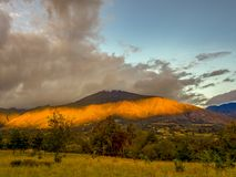 A stripe of light on the Andean mountains of central Colombia. The orange sunset beams of light go trought the clouds projecting a stripe of light on the Andean royalty free stock photos