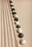 Stripe of white and black stones lying on the sand. Can be used as a background stock images