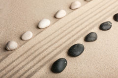 Stripe of white and black stones lying on the sand Stock Photography