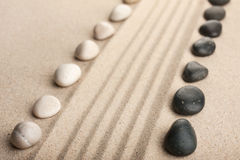 Stripe of white and black stones lying on the sand Stock Photo
