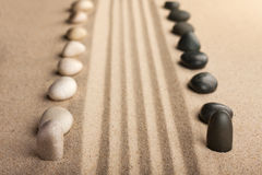 Stripe of white and black stones lying on the sand Royalty Free Stock Photography