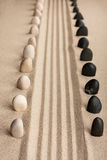 Stripe of white and black stones sticking of the sand Stock Photography