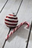 Striped безделушка рождества и тросточка конфеты на деревянной предпосылке Стоковые Изображения