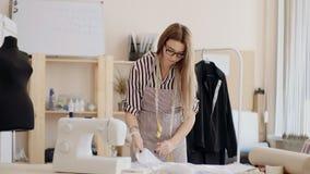 Striped возникновение, стекла, рисберма и куртка белошвейки девушки кавказское, осторожно кладут на его ткань стола на видеоматериал