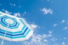 Striped зонтик пляжа под голубым небом Стоковая Фотография