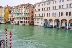 Striped и деревянные причаливая поляки и красочные венецианские здания готической архитектуры в Венеции, Италии стоковое фото rf