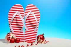 Striped кувырки и орнаменты рождества на тропическом пляже стоя на песке против солнечного голубого неба с космосом экземпляра Стоковая Фотография