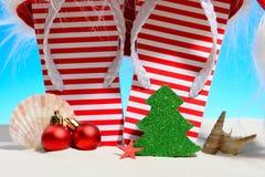 Striped кувырки и шляпа Санты на тропическом пляже Стоковое Фото