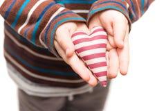 Striped сердце в руках маленького ребенка Стоковое Изображение