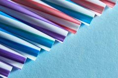 Striped соломы питья других цветов в строке изолированной на голубой предпосылке Стоковое Фото