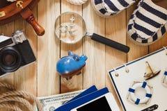 Striped тапочки, копилка, телефон и морские украшения, деревянная предпосылка Стоковая Фотография