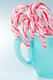 Striped тросточки конфеты в свете - голубая чашка Стоковое Изображение