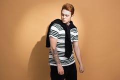 Стильный рыжеволосый парень в striped рубашке с татуировкой на его руке представляет с черным свитером на его плечах на стоковое изображение rf