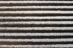 Striped background. Brown wood texture covered with white snow Royalty Free Stock Photo