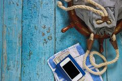 Striped bag, phone and maritime decorations on the wooden background Stock Image