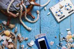 Striped bag, wheel, phone and maritime decorations on the wooden background Royalty Free Stock Photography