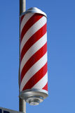 Striped barbers pole. Set against bright blue sky Stock Images