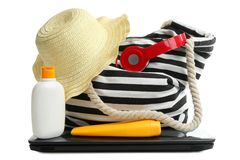 Striped beach bag with red headphones, laptop and different beach accessories. One striped beach bag with red headphones, laptop and different beach accessories stock photo