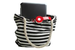 Striped beach bag with red headphones and laptop. One striped beach bag with red headphones and laptop isolated on white. Concept summer, work on vacation royalty free stock photography